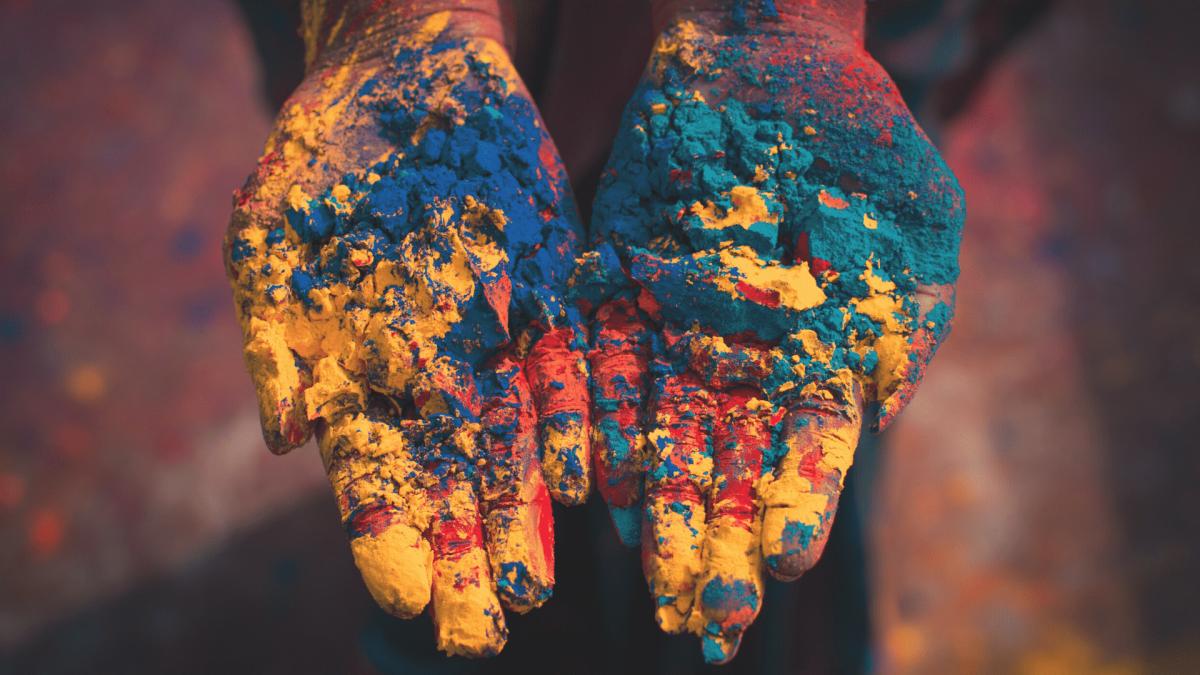 dłonie w kolorowym proszku